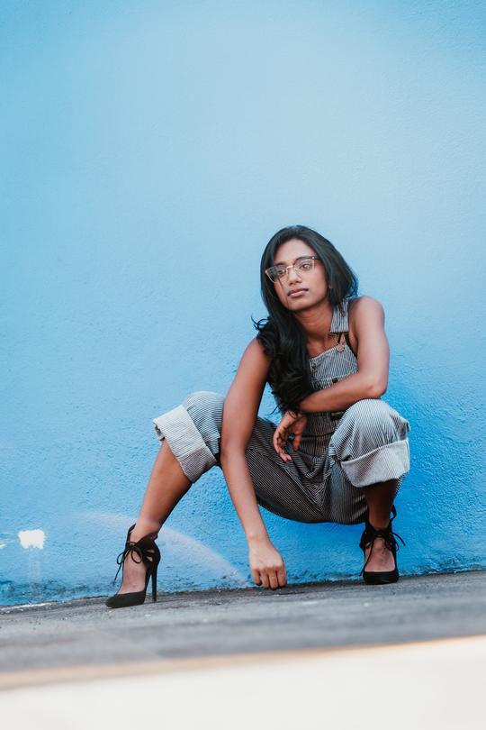 woman-crouching-by-blue-wall-portrait_540x
